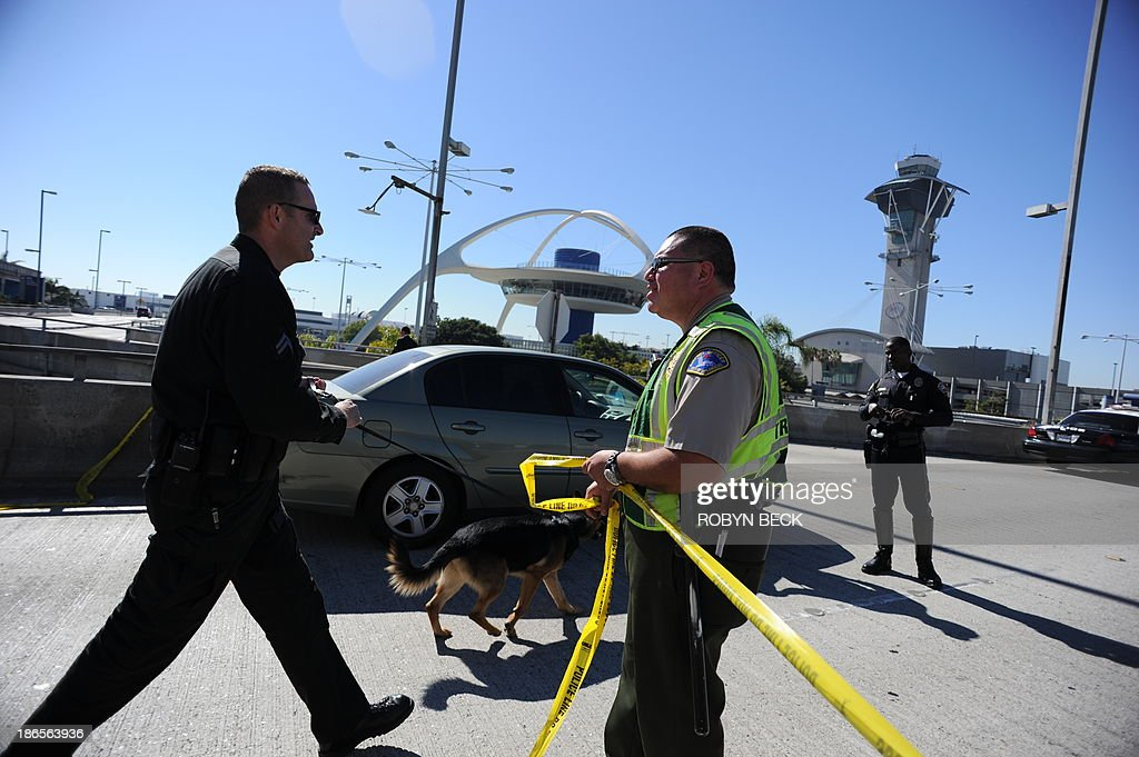 A K-9 officer (L) crosses a crime tape line on November 1, 2013 after a gunman reportedly opened fire at a security checkpointin Los Angeles International Airport. Police believe a gunman who opened fire at Los Angeles airport Friday acted alone, a police chief said, while not confirming reports that the shooter and one victim were killed. 'We believe at this point that there was a lone shooter, that he acted,' said Patrick Gannon, head of the LAX police force, saying he 'was the only person who was armed in this incident.' Seven people were injured, including six taken to hospital, said the head of the LA Fire Department James Featherstone, briefing reporters for the first time a couple of hours after the incident.