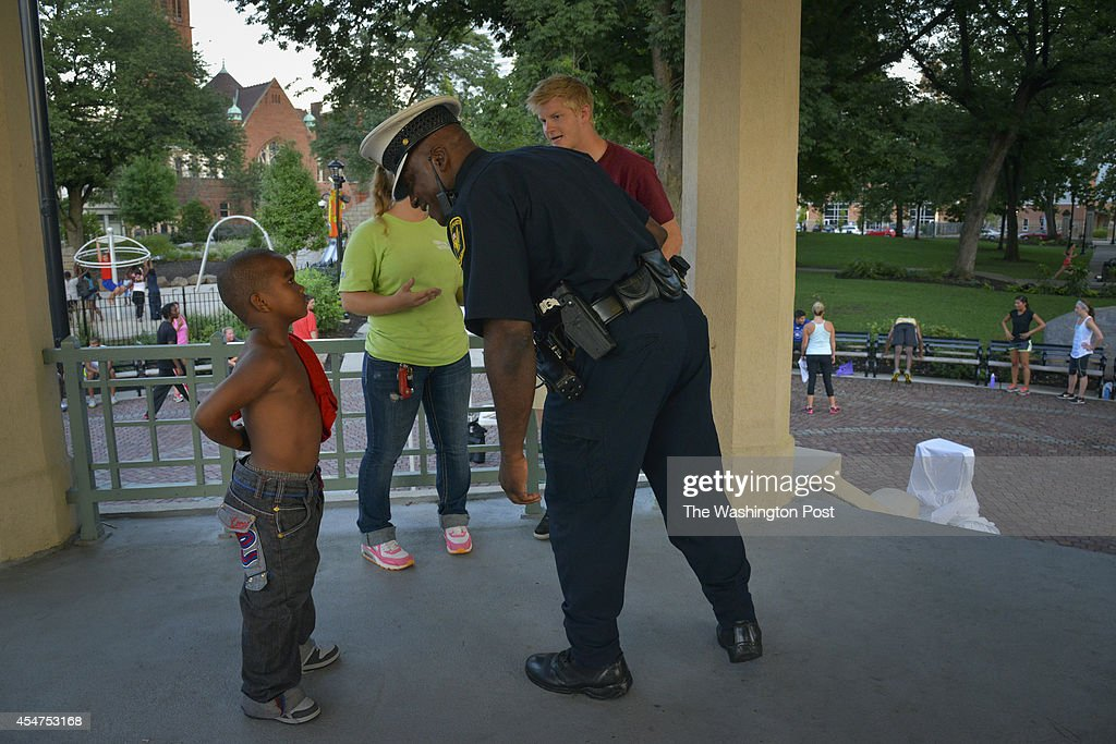 Officer Darryl Hardy with the Cincinnati Police Department tries to convince young Michael Nixson that it is good to wear a belt at Washington Park...