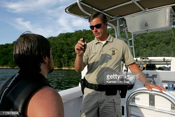 Officer Dean Bartlett with the Missouri Water Patrol conducts a field sobriety test on a boater inside Party Cove at the Lake of the Ozarks in...