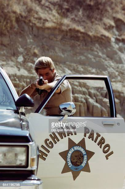 Officer Denise Daeley of the California Highway Patrol positions herself against the open door of her patrol car while aiming her shotgun