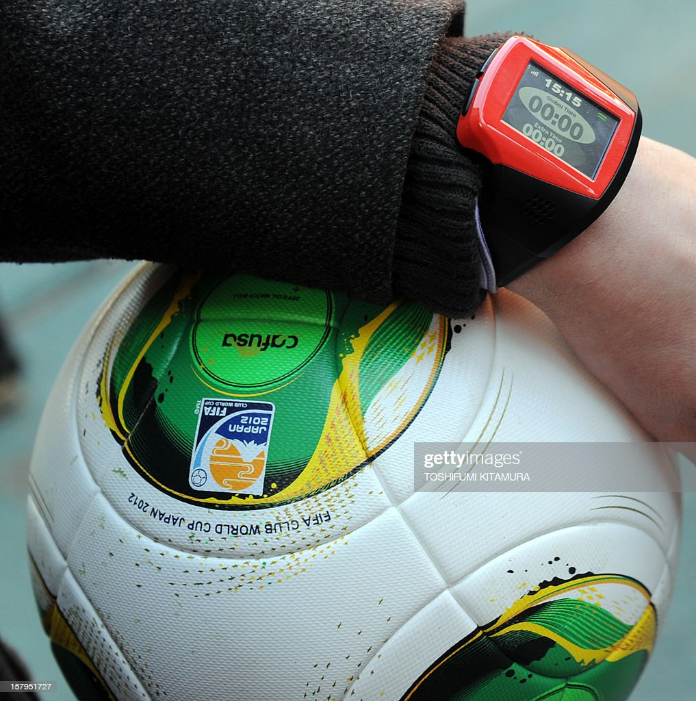 A FIFA officer displays a watch displaying 'goal' and a ball during a demonstration of new goal-line technology by Hawk-Eye Innovations at Toyota Stadium in Toyota, Aichi prefecture on December 8, 2012 which is being used in the 2012 Club World Cup tournament in Japan. Hawkeye, which is familiar from tennis and cricket and uses cameras to track a ball's position and trajectory, will be tested at the competitions in Toyota. The ninth edition of the FIFA Club World Cup football tournament is taking place from December 6 to 16. AFP PHOTO / TOSHIFUMI KITAMURA