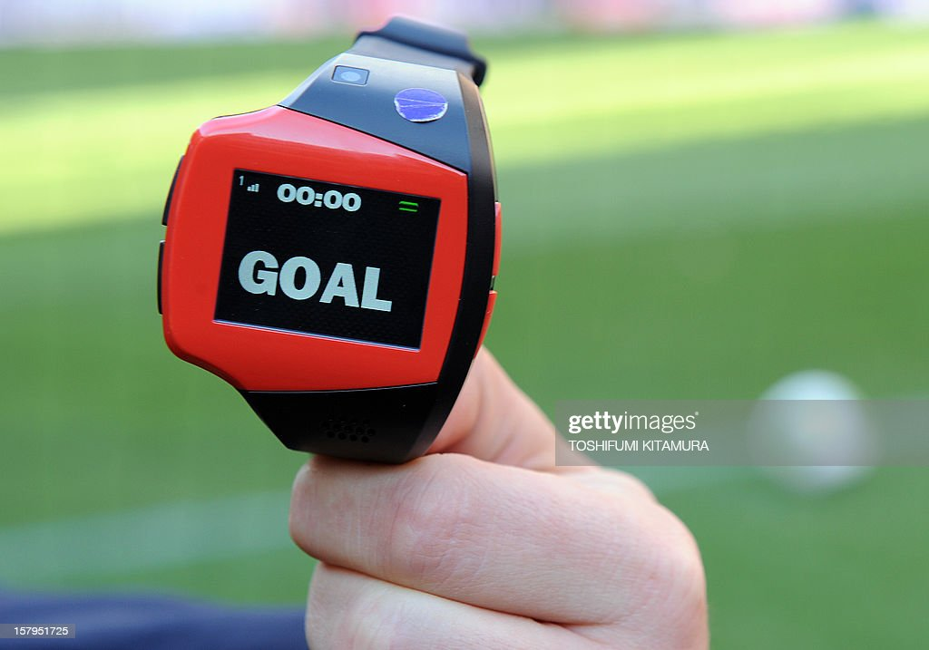 A FIFA officer displays a watch displaying 'goal' during a demonstration of new goal-line technology by Hawk-Eye Innovations at Toyota Stadium in Toyota, Aichi prefecture on December 8, 2012 which is being used in the 2012 Club World Cup tournament in Japan. Hawkeye, which is familiar from tennis and cricket and uses cameras to track a ball's position and trajectory, will be tested at the competitions in Toyota. The ninth edition of the FIFA Club World Cup football tournament is taking place from December 6 to 16.