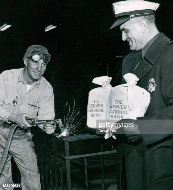 Officer George Curnow holds $38000 as it is transferred to new Denver US National Bank Welder Jess Shuler watches the bags as he uses cutting torch...