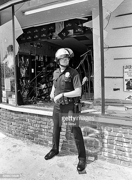 A LAPD officer in front of a looted record store in South Central LA Los Angeles has undergone several days of rioting due to the acquittal of the...