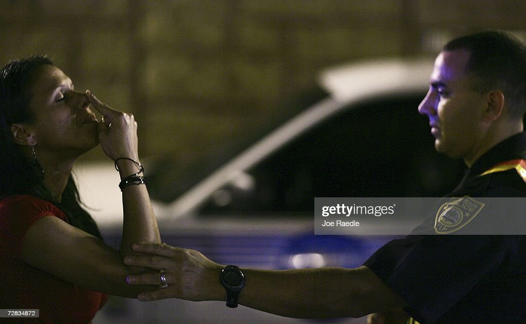 Officer Kevin Millan from the City of Miami Beach police department helps steady a woman during a field sobriety test at a DUI sobriety traffic checkpoint December 15, 2006 in Miami, Florida. According to police, the woman failed a breathalyzer test by blowing into the device and receiving two readings one at .190 the other .183, which is twice the legal limit in Florida. The city of Miami, with the help of other police departments, will be conducting saturation patrols and setting up checkpoints during the holiday period looking to apprehend drivers for impaired driving and other traffic violations.