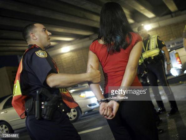 Officer Kevin Millan from the City of Miami Beach police department arrests a woman after she failed a field sobriety test at a DUI checkpoint...