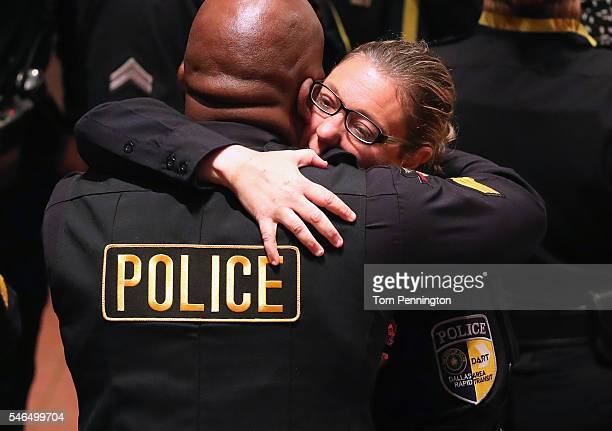DART officer Misty McBride hugs a fellow officer before an interfaith memorial service honoring five slain police officers at the Morton H Meyerson...