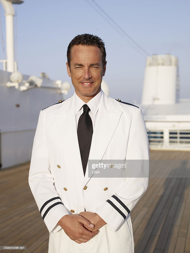 Officer standing on deck of cruise ship, smiling