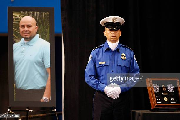 TSA officer stands in front of a poster of slain TSA officer Gerardo Hernandez during a public memorial for Transportation Security Administration...