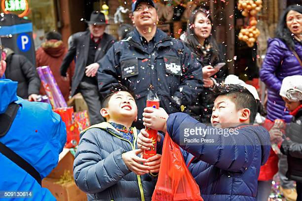 NYPD officer supervises youngsters firing off confetti cannon on Bayard Street Much of Lower Manhattan came alive in sound and color as the Year of...