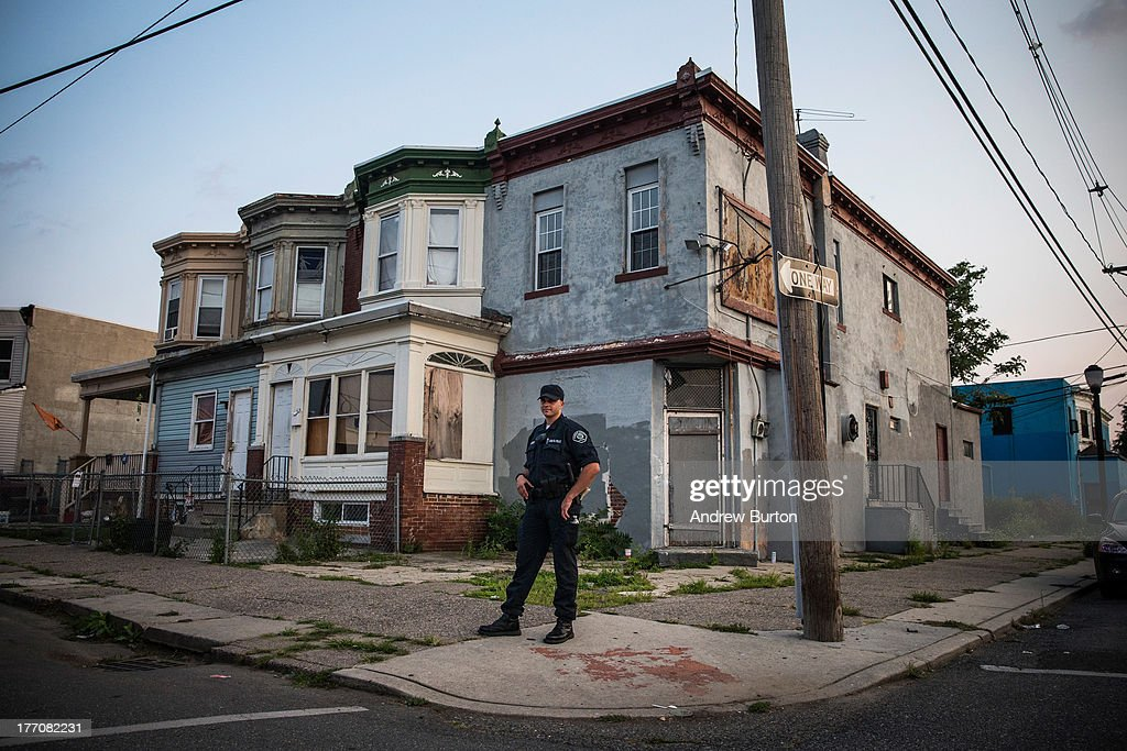 Officer Tom Rambone, of the Camden County Police Department (CCPD), goes on a foot patrol on August 20, 2013 in the East Camden neighborhood of Camden, New Jersey. The town of Camden, which was once a large industrial town but watched it's population dwindle as manufacturing left, has been marred with societal problems including high unemployment, crime, murder and heavy drug trafficking for decades. The Camden County Police Department was officially created in May, 2013, after the unionized Camden Police department was disbanded. The overhaul, which was supported by New Jersey Governor Chris Christie, has been considered unprecendented and has been closely watched around the country. The new force currently has approximately 280 members, and will reach full size by December, with 400 members. Early signs suggest the overhaul has been effective - The Wall Street Journal reported earlier this month that Camden murder rates fell 29% from May, 2013 to July 2013, compared to the same period last year. Absentee rates of the CCPD is also lower: approximately 5% of officers have been reported absent so far, compared to approxmiately 30% of the Camden Police Department prior to the change in command.