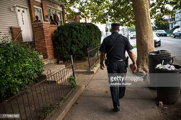 Officer Troy Redd of the Camden County Police Department goes on a foot patrol on August 20 2013 in the East Camden neighborhood of Camden New Jersey...