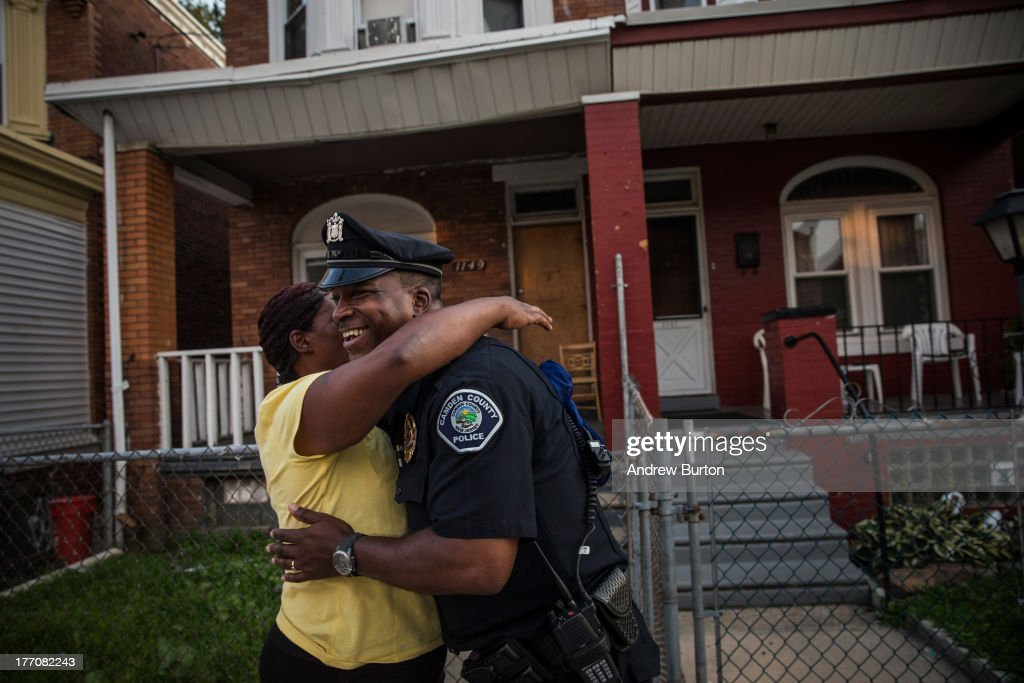 Officer Troy Redd, of the Camden County Police Department (CCPD), talks with a woman while on a foot patrol on August 20, 2013 in the East Camden neighborhood of Camden, New Jersey. The town of Camden, which was once a large industrial town but watched it's population dwindle as manufacturing left, has been marred with societal problems including high unemployment, crime, murder and heavy drug trafficking for decades. The Camden County Police Department was officially created in May, 2013, after the unionized Camden Police department was disbanded. The overhaul, which was supported by New Jersey Governor Chris Christie, has been considered unprecendented and has been closely watched around the country. The new force currently has approximately 280 members, and will reach full size by December, with 400 members. Early signs suggest the overhaul has been effective - The Wall Street Journal reported earlier this month that Camden murder rates fell 29% from May, 2013 to July 2013, compared to the same period last year. Absentee rates of the CCPD is also lower: approximately 5% of officers have been reported absent so far, compared to approxmiately 30% of the Camden Police Department prior to the change in command.