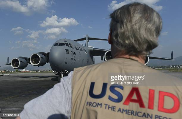A USAID officer watches as a US military C17 cargo plane taxis to a stop at Kathmandu's international airport on May 3 2015 International aid...
