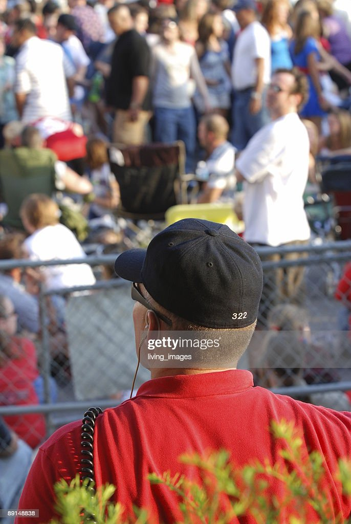 Officer watching over crowd : Stock Photo