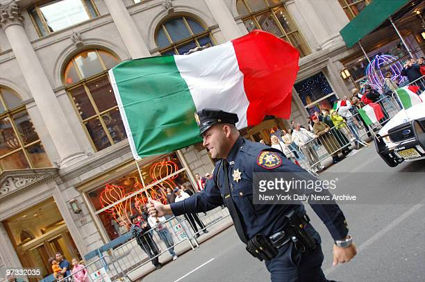 Officer with the Hudson County NJ sheriff's office waves an Italian flag as he marches in the 61st Annual Columbus Day Parade along Fifth Ave