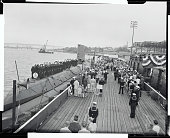 Officers and crew of the submarine Nautilus stand at attention as the national anthem is played and the flag is raised over the world's first nuclear...