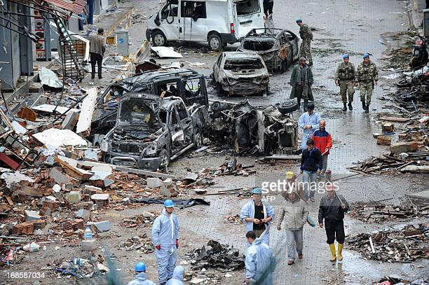 Officers and members of the military walk near damaged cars on May 12 2013 on a street hit by a car bomb explosion which went off on May 11 in...