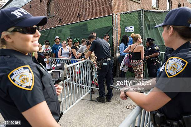 NYPD officers check bags at an entrance to Brooklyn Bridge park along the East River before the Macy's Fourth of July Fireworks on July 4 2015 in the...