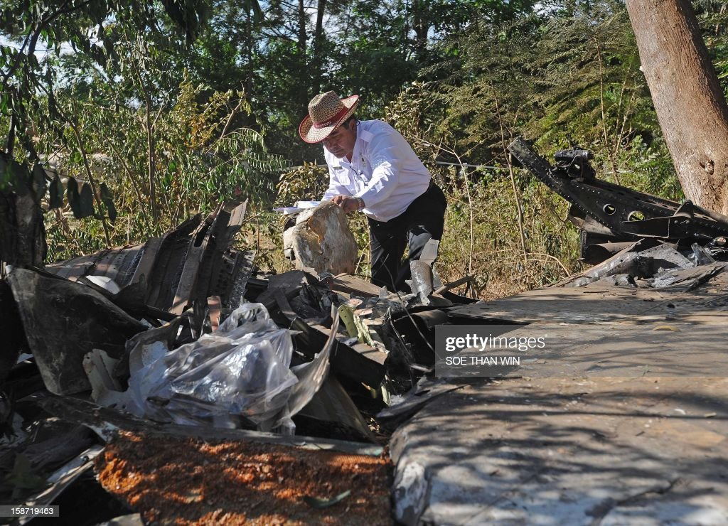 Officers from the Department of Civil Aviation inspect the remains of a plane that crash landed the day before near Heho airport in the southern Shan state on December 26, 2012. Myanmar was investigating the cause of an air accident that left two people dead and 11 injured when a passenger jet packed with foreign tourists crash-landed and caught fire. AFP PHOTO/Soe Than WIN