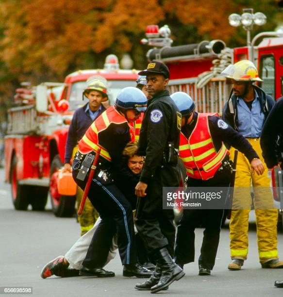 Officers from the US Capitol Police drag a handcuffed protestor on a road outside the eastern facade of the Capitol building Washington DC October...