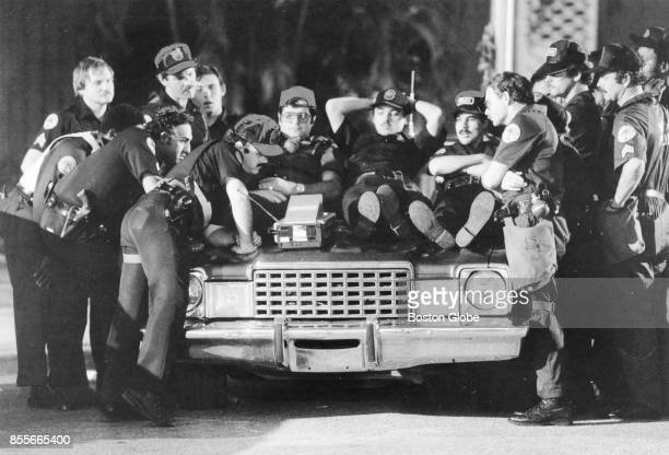 Officers gather to watch a television on the hood of a car in a holding area in Miami on Dec 31 1982