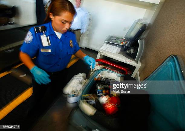 TSA officers hand inspect a traveler's baggage after an alarm sounded on one of the xray machines The officer did not find anything and sent the...