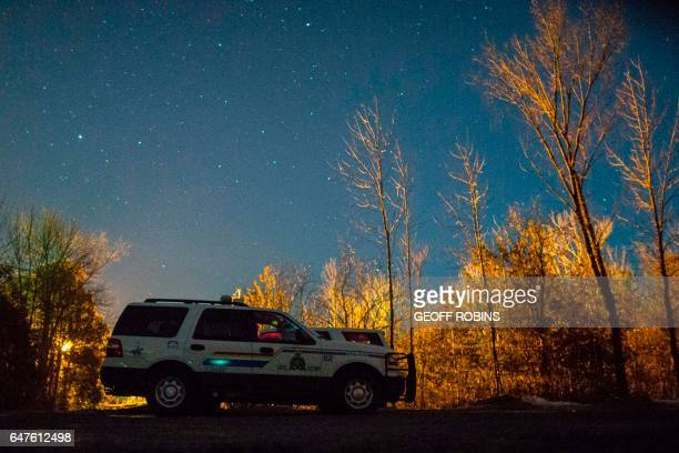 RCMP officers keep watch at the Canada/US border near Hemmingford Quebec February 26 2017 Canada's Prime Minister Justin Trudeau is facing growing...