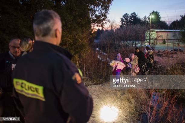 RCMP officers look on as an extended family of seven people from Turkey illegally cross the USCanada border just before dawn on February 28 2017 near...