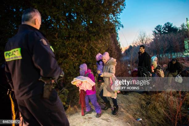 TOPSHOT RCMP officers look on as an extended family of seven people from Turkey illegally cross the USCanada border just before dawn on February 28...
