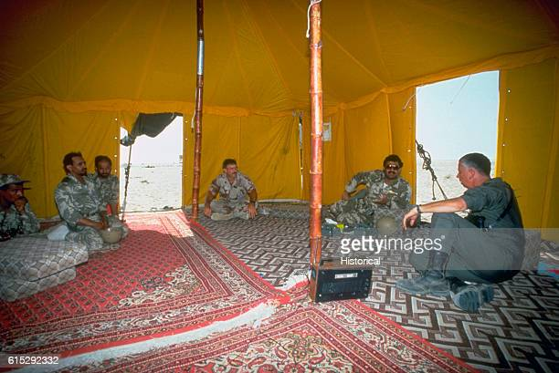 US officers meet with Colonel Turki Al Firm and his staff in a tent during Operation Desert Shield Saudi Arabia ca 1990