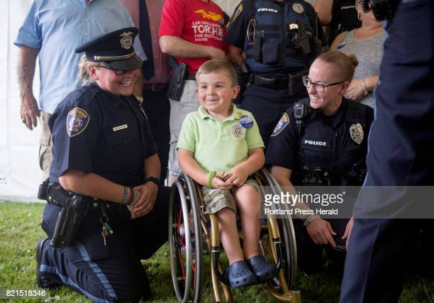 Officers Melissa May at left and Jaci Lorenzen pose with fiveyearold Kellan Tilton in a photo with all of the law enforcement personnel who are...