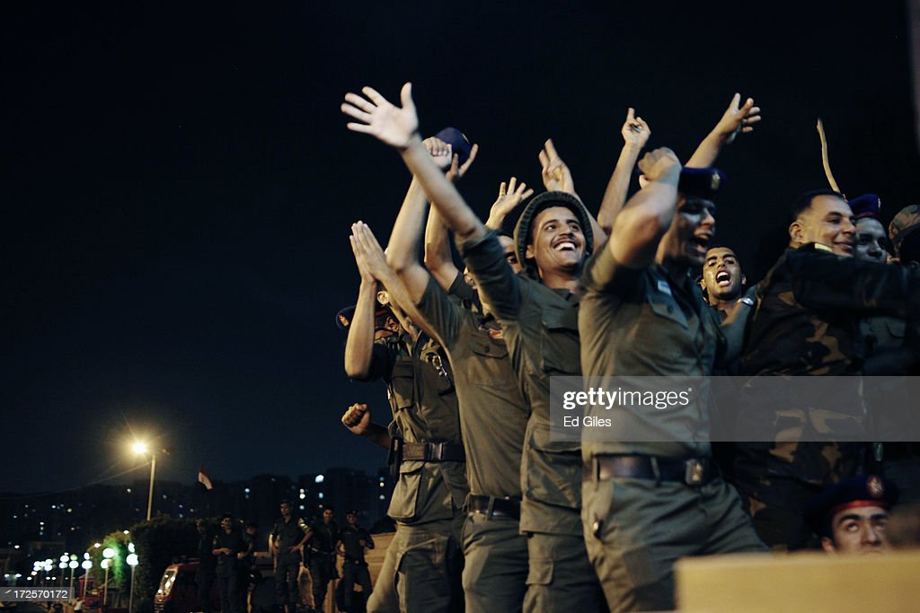 Officers of the Egyptian Republican Guard celebrate at the gates of the Republican Guard headquarters in the suburb of Nasr City after a broadcast by...