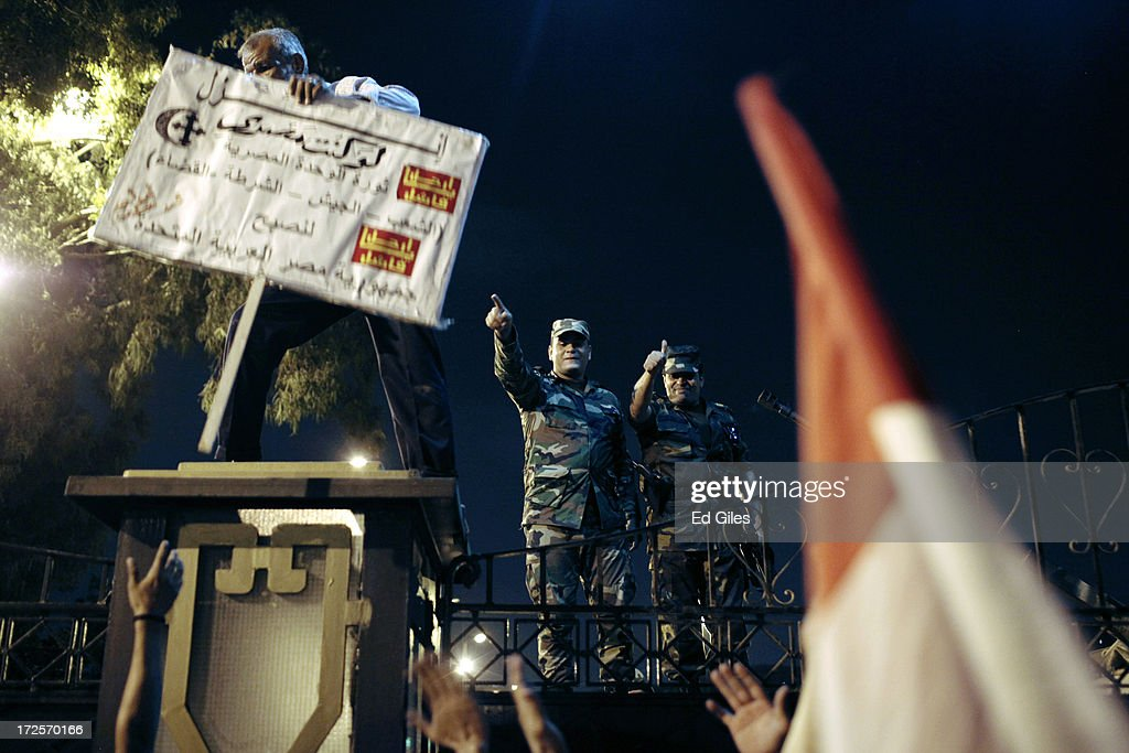Officers of the Egyptian Republican Guard gesture to protesters at the gates of the Republican Guard headquarters in the suburb of Nasr City after a...