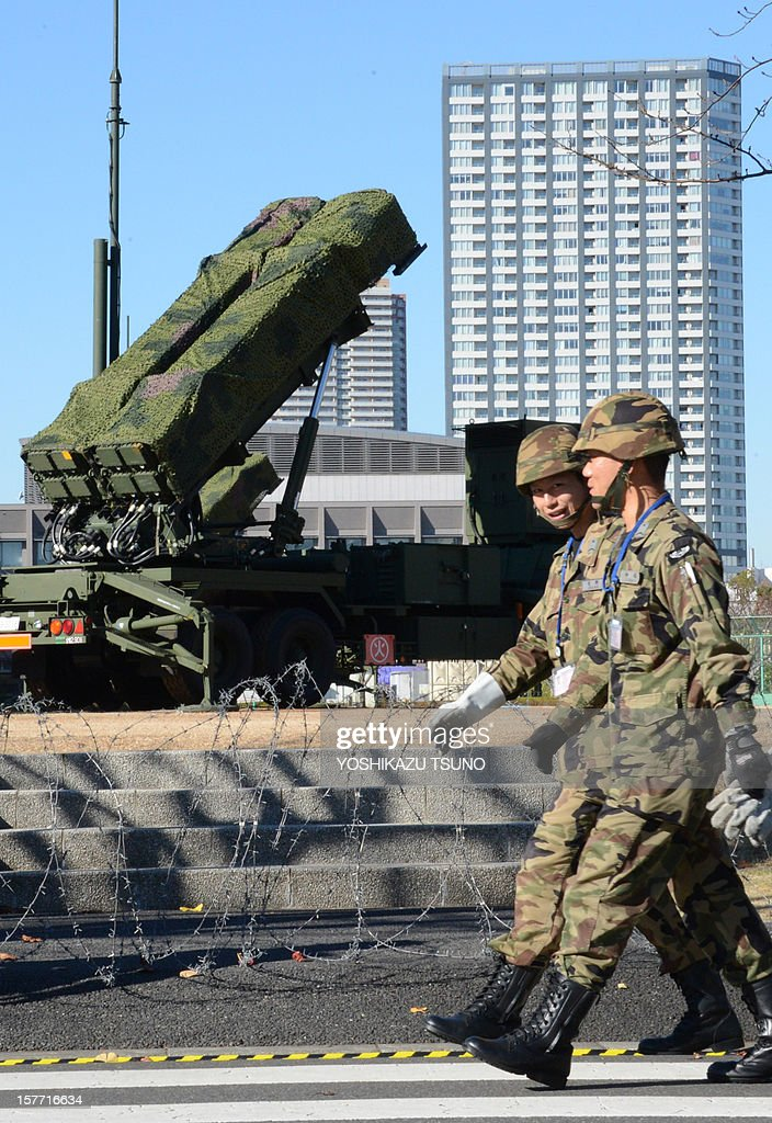 Officers of the Ground Self-Defense Force (SDF) walk in front of Japan's SDF set Patriot Advanced Capability-3 (PAC-3) missile launcher at the Defence Ministry in Tokyo on December 6, 2012. Japan on December 6 dispatched three destroyers to waters over which North Korea says its satellite-bearing rocket will travel. In Tokyo, the defence ministry has deployed another PAC-3 battery at its headquarters as part of its effort to intercept anything headed towards the Japanese mainland. AFP PHOTO / Yoshikazu TSUNO