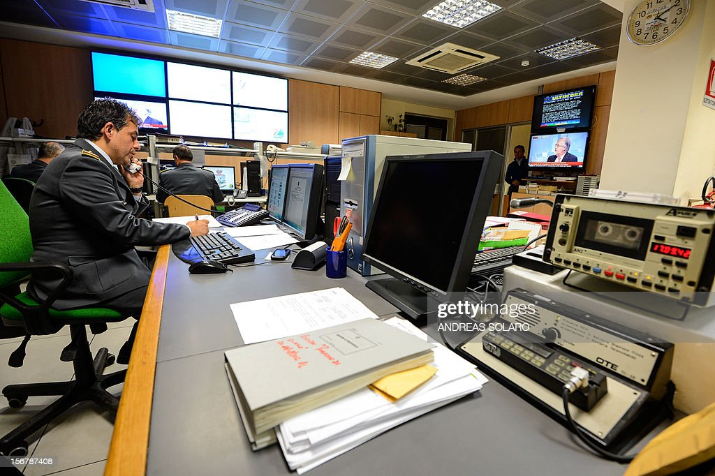 Officers of the Guardia di Finanzia, speak on the telephone in the operation room of the regional comando of the Lazio area on November 20, 2012 in Rome. The operation room of the Guardia di Finanza receives phone calls and launches operations related to tax abuses and tax controls. AFP PHOTO / ANDREAS SOLARO