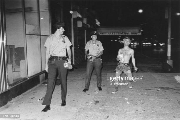 Officers of the NYPD 9th Precinct cast an amused glance at an eccentric passerby on 2nd Avenue East Village New York City 1978