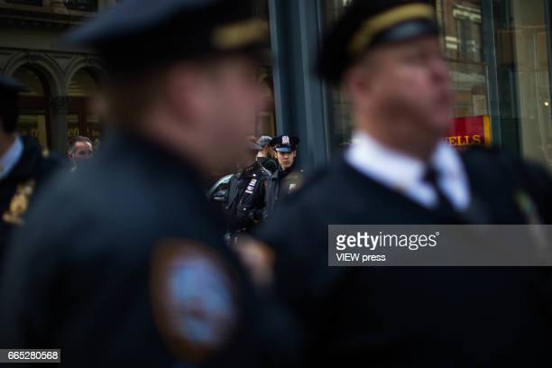 NYPD officers patrol outside a Wells Fargo bank as indigenous peoples and activists begin the overnight camp out in front of the branch on April 5...