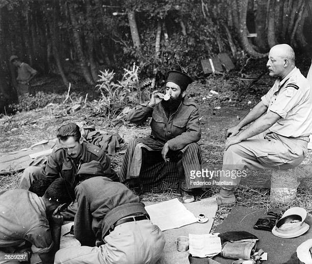 Officers plan the assault on Mount Kiapha at Mount Lyoku during the Greek Civil War while a Greek Orthodox priest drinks coffee Each brigade has a...