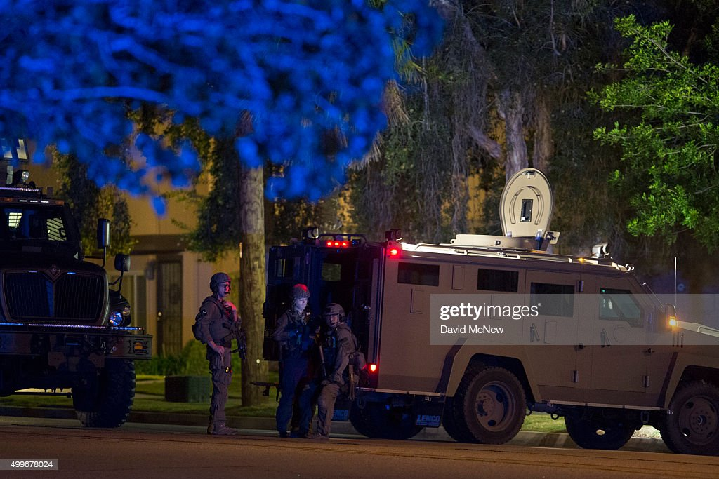 Officers prepare to raid the home of one or more suspects of a mass shooting at the Inland Regional Center by multiple gunmen on December 2 2015 near...