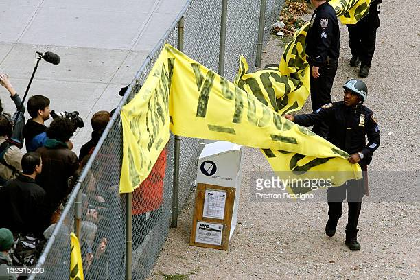 NYPD officers pull down signage as they clear out Occupy Wall Street activists from a private park next to Duarte Square on November 15 2011 in New...