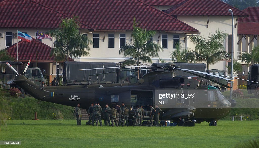 Officers stand by a Royal Malaysian Air Force Sikorsky S-61 helicopter in Cenderawasih on March 5, 2013, near Tanduo, where Malaysia launched an assault with fighter jets bombing the standoff village followed by a ground assault by troops. Malaysia's military on March 5 launched a fierce assault including jet fighters on up to 300 Filipino intruders after a deadly three-week standoff, as their leader vowed they would fight to the death. AFP PHOTO / MOHD RASFAN