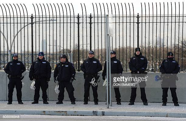 NYPD officers stand by as New York airport workers march to the airport during a protest and 'civil disobedience' January 18 2016 near LaGuardia...