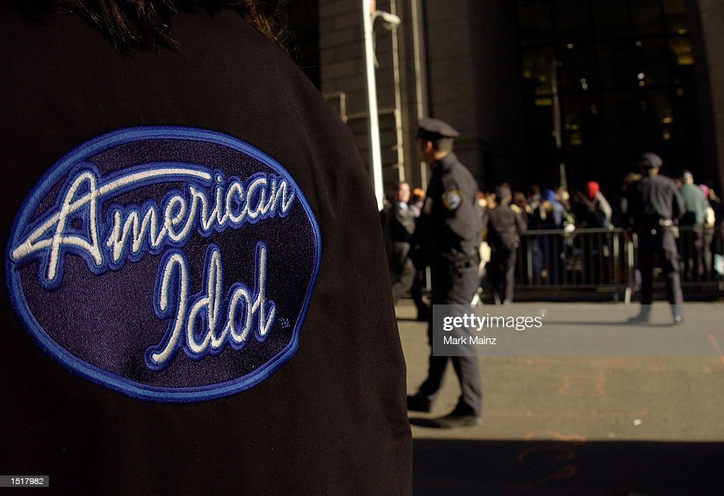 NYPD officers stand guard as hundreds wait outside the Regent Hotel Wall Street to audition for 'American Idol' October 24 2002 in New York City