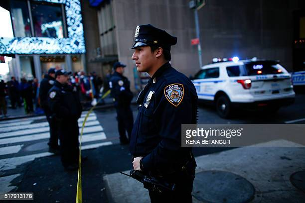 NYPD officers stand guard in Times Square after it was evacuated after a suspicious package call in New York on March 28 2016 Investigators from the...