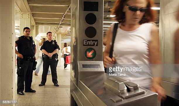 NYPD officers watch a turnstile in the Times Square subway station July 21 2005 in New York City Four small explosions hit London's transport network...