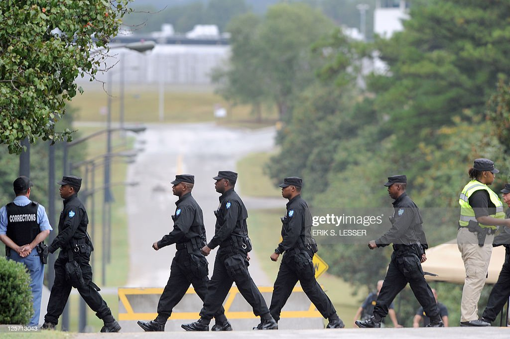 Officers with the Georgia Department of Corrections walk into designated protest areas outside the Georgia Diagnostic and Classification Prison in...