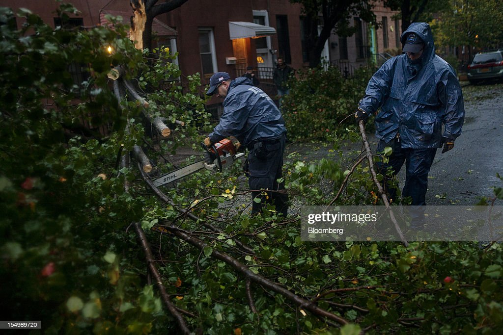 Officers with the New York City Police Department (NYPD) Emergency Services Unit cut away a fallen tree in the Red Hook neighborhood of Brooklyn in New York, U.S., on Monday, Oct. 29, 2012. Hurricane Sandy, the Atlantic's Ocean's biggest-ever tropical storm, barreled toward southern New Jersey after bringing a region with 60 million residents to a virtual standstill and upending the U.S. presidential race eight days before Election Day. Photograph: Victor J. Blue/Bloomberg via Getty Images