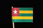 A official and original flag of Togo on toothpick on black background. It has five bands of green alternating with yellow and red field with star.
