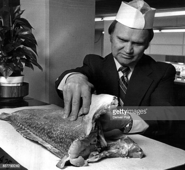 FDA official Douglas Payne inspects fresh salmon for firmness of flesh that is not separated from back Credit Denver Post